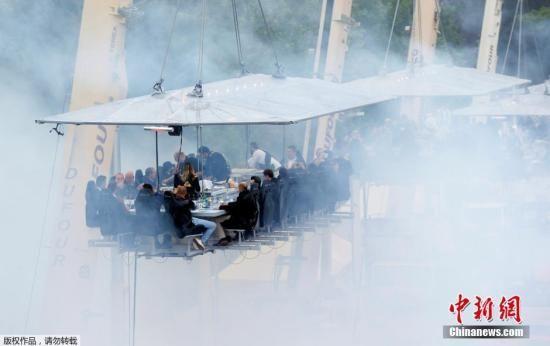 当地时间6月1日,比利时布鲁塞尔,多台起重机将能容纳多人的大餐桌悬挂在距离地面40米的高空。
