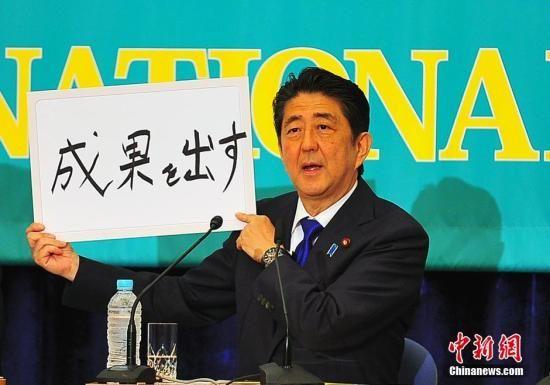 """日本参议院选战在即,6月21日在日本记者俱乐部进行的选前党首辩论会上,""""安倍经济学""""的成败功过再度成为热辩之题。图为安倍现场高调亮出""""搞出成果""""字牌。"""