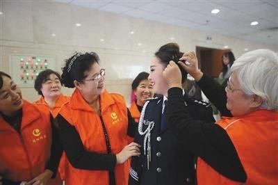 """在活动现场,""""朝阳群众""""中的几位阿姨帮民警整理头发。警方供图"""
