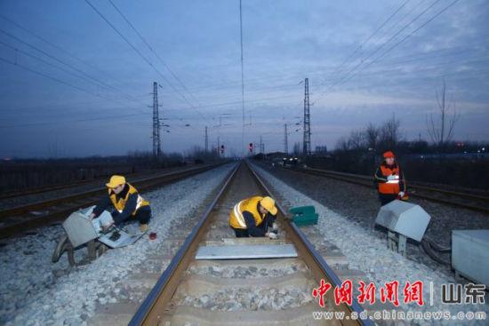 图为作业人员检查轨旁设备,现场防护员与驻站联络员呼唤应答,确认无列车通过。