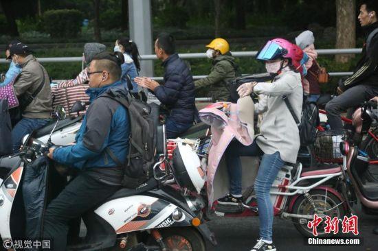 2018年10月9日,山东济南,昨日一场秋雨过后开始降温,今天清晨最低气温只有6度,马路上不少上班族穿上羽绒服骑车赶上班路。 图片来源:视觉中国