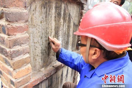 图为工人用丙酮、酒精擦拭、修复孟庙内的石碑。 曾洁 摄