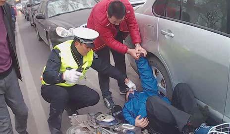 民警和好心市民正在救助突发病的男子。