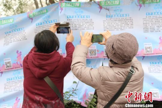 济南千佛山三月三相亲会现场,代子女相亲的老人在写有相亲信息的横幅前拍照记录。 赵晓 摄