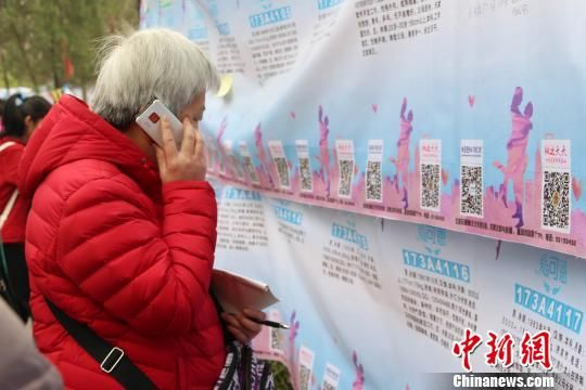 参加济南千佛山三月三相亲会,代子女相亲的老人现场通过电话向子女介绍相亲对象情况。 赵晓 摄