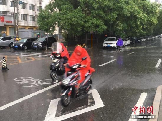 资料图 北京阜成路,市民雨中骑行。 中新网记者 富宇 摄