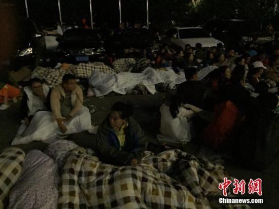 图为九寨沟景区内,许多游客不敢继续待在酒店内,裹着厚衣服和毛毯来到街上席地而睡。 徐广 摄