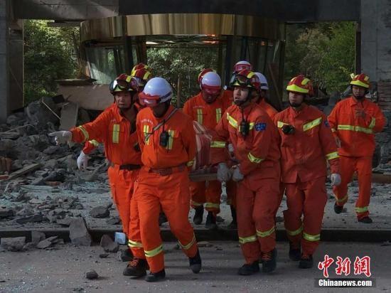 8月8日21时19分在四川阿坝州九寨沟县发生7.0级地震,震源深度20千米。图为8月9日,救援人员从受损建筑中救出一人。中新网记者 刘忠俊 摄