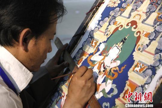 唐卡大师平措扎西在展览现场给未完成的唐卡作品填色。 沙见龙 摄
