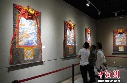 参观者驻足欣赏唐卡作品。 沙见龙 摄