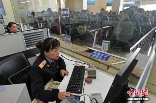 资料图:山西太原火车站售票大厅,工作人员在向旅客发售车票。中新社记者 武俊杰 摄
