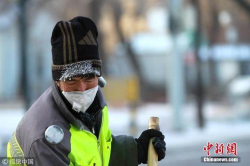 资料图:2017年11月18日,黑龙江省哈尔滨市,清晨时的温度达到-17℃。一些在室外时间长些的市民、保洁员,口罩与帽子上挂着哈气结成的白霜。图片来源:视觉中国