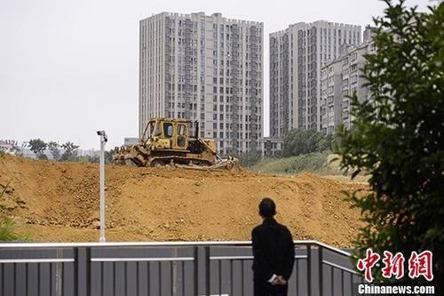 资料图:市民观望一楼盘工地上的推土机作业。中新社记者 杨华峰 摄