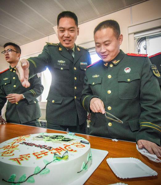 """面对战友们精心设计的祝福蛋糕,身经百战的老班长竟不舍得""""下手""""了! 陈镜旭 摄"""