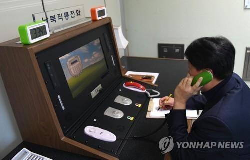 当地时间1月3日下午3点34分,在板门店联合警备区联络事务所,韩方联络官拿起韩朝直通电话的话筒与朝方通话。(图片来源:韩联社)