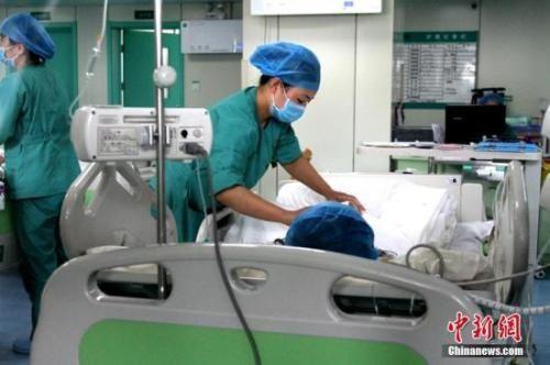 资料图:医护人员在给患者治疗。 中新社记者 田进 摄
