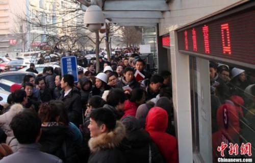 资料图:北京朝阳区房屋登记发证大厅外排队领号准备办理过户手续的市民。 韩海丹 摄
