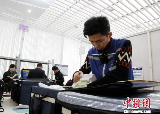 """12306网络订餐济南西站配送中心的""""外卖小哥""""正在整理配送箱。 沙见龙 摄"""