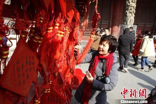 """2月8日,""""孔府过大年""""活动在山东曲阜举行。图为游客悬挂祈福牌。 沙见龙 摄"""