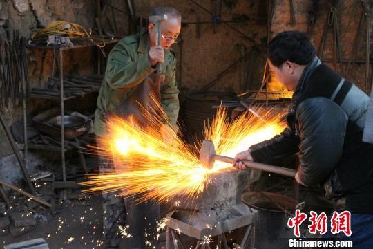 图为牛祺圣和儿子牛大伟正在家中的铁匠铺打铁。 赵晓 摄