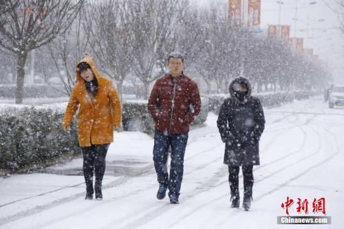 资料图:2016年3月9日,受强冷空气影响,甘肃多地出现降雪、降温天气。图为市民在雪中行走。 陈飞 摄