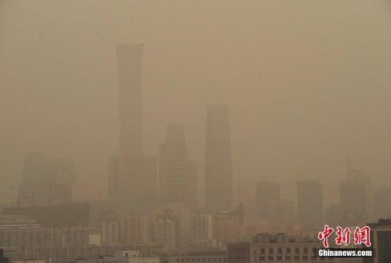 资料图:北京CBD地区的高层建筑笼罩在雾霾和扬沙天气中。中新社记者 贾天勇 摄