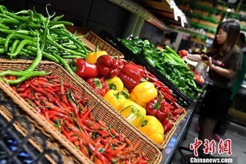 图为市民在超市选购蔬菜。中新社记者 张斌 摄