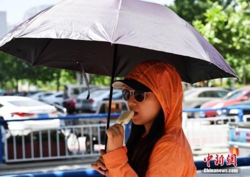 6月5日中午,河北石家庄户外温度达到38℃,市民们出行时携带各种遮阳护具。中新社记者 翟羽佳 摄