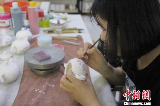 图为画家们在茶壶上进行农民画创作。 赵晓 摄