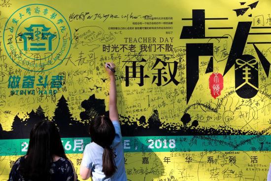 毕业生在毕业学子留言墙上写下寄语。