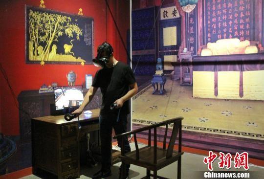 展览融入现代科技元素,特设VR互动区。图为参加活动的媒体记者体验VR技术。 赵晓 摄