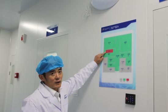 图为工作人员介绍厂房内的生产运作流程。赵晓