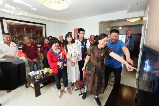 """沙丽(前排左一)和丈夫赵军(前排右一)在新中国70周年的阅兵方队中看到了姑娘赵婧涵,兴奋的指给大家看。""""快看,仪仗队空军方队后排右边第五个!""""曲记鹏拍摄"""