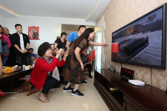 """沙丽(右一一)和丈夫赵军(右二)在新中国70周年的阅兵方队中看到了姑娘赵婧涵,兴奋的指给大家看。""""快看,仪仗队空军方队后排右边第五个!""""曲记鹏拍摄"""