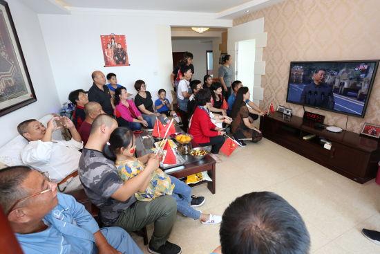 图为:沙丽全家围坐在电视机前,收看大会直播--曲记鹏