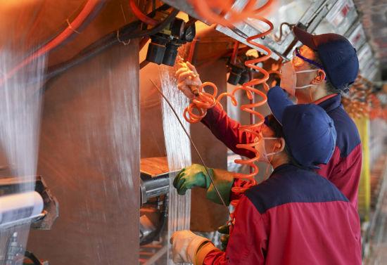 """山能临矿玻纤集团8万吨数字化生产线窑炉产品车间员工正在进行引丝操作,引丝经过慢拉系统,实现了自动""""上车"""",在提高效率的同时降低了工人劳动强度。"""