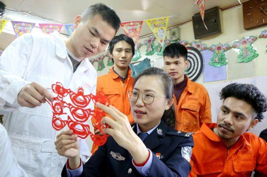 黄岛边检站民警向船员展示剪纸作品(吴绍洋 摄)