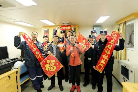 青岛出入境边防检查站民警与船员一起给全国人民拜早年(王培锋 摄)