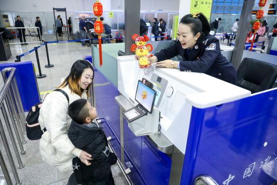 烟台边检站民警为入境的小旅客送上鼠年吉祥玩偶 ( 李通 摄)