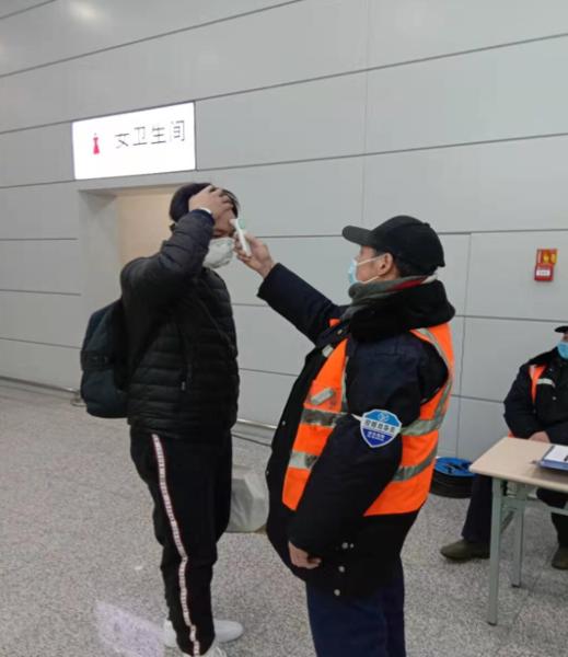 配合车站工作人员进行旅客体温检测。