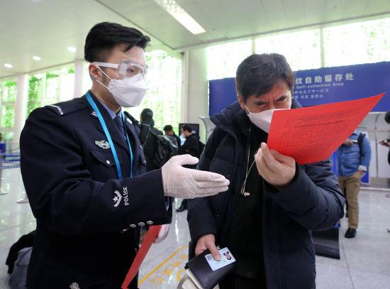 济南边检站民警为外籍返程复工旅客赠送《复工防疫指南》(沈泰 摄)