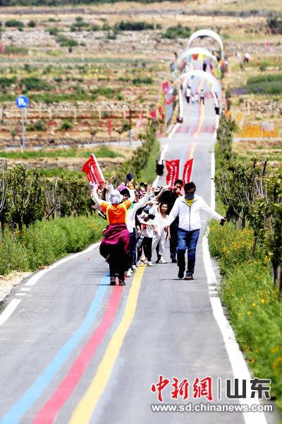 在一家玫瑰加工企业的生态产业园内,一群游客在田间道路上唱跳自如,欢呼雀跃。沙见龙 摄