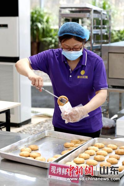 工作人员将现烤的玫瑰鲜花饼送给游客品尝。沙见龙 摄