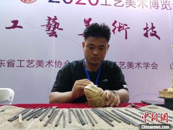 洪福禄是一名木雕师,正在现场手持刻刀,对照着金蝉标本雕刻摆件。 郝学娟 摄