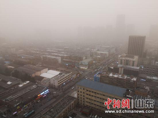 """15日,沙尘天气已经""""到访""""山东。省会济南街头行人戴着口罩、裹紧衣服,步履匆匆。沙见龙 摄"""