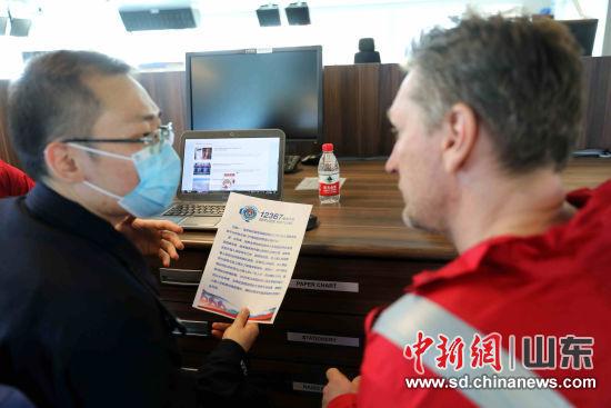 在烟台蓝鲸二号钻井平台,烟台出入境边防检查站民警向外籍船员宣传12367热线电话使用方法。